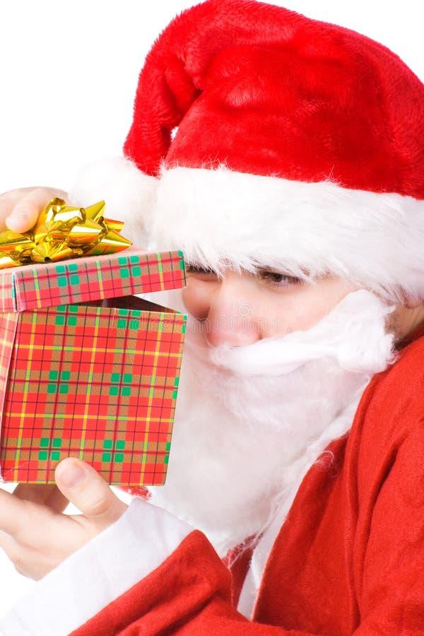 Papá Noel que mira en el rectángulo de regalo fotos de archivo libres de regalías
