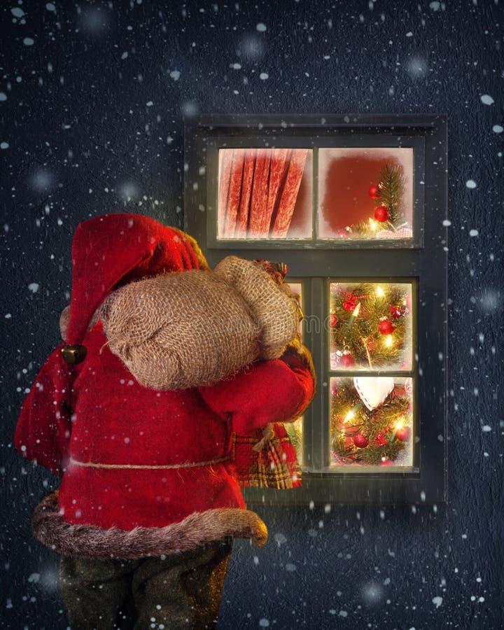Papá Noel que mira a través de una ventana imagen de archivo