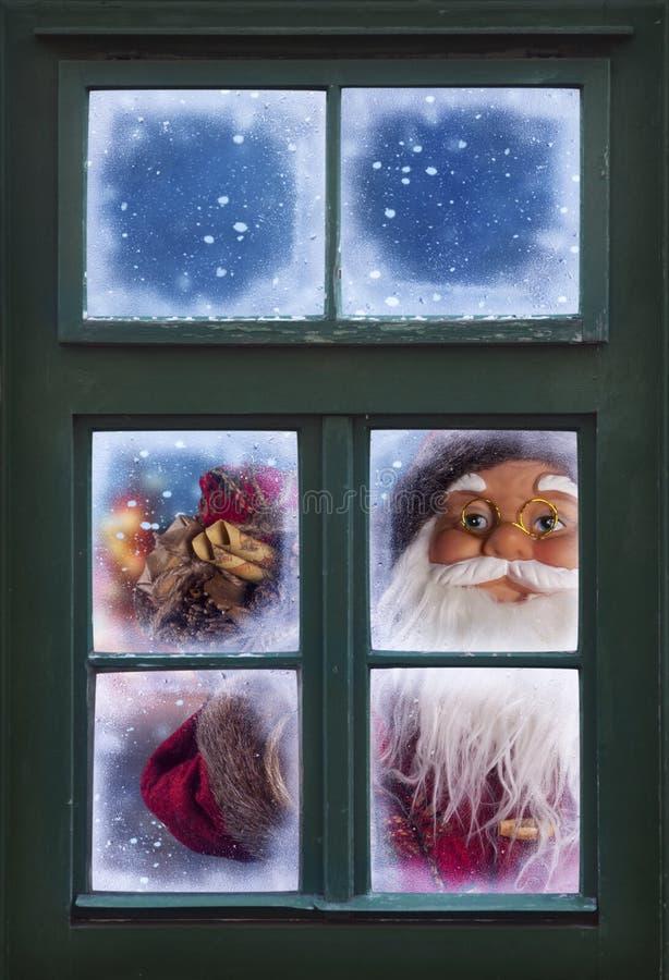 Papá Noel que mira a través de una ventana foto de archivo libre de regalías
