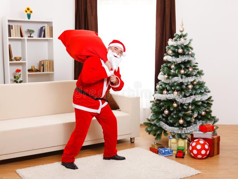 Papá Noel que recorre con el bolso lleno fotografía de archivo libre de regalías