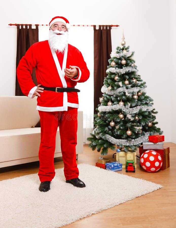 Papá Noel que se coloca delante del árbol de navidad fotografía de archivo