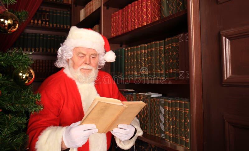Papá Noel que se coloca en el árbol de navidad y que lee un libro foto de archivo