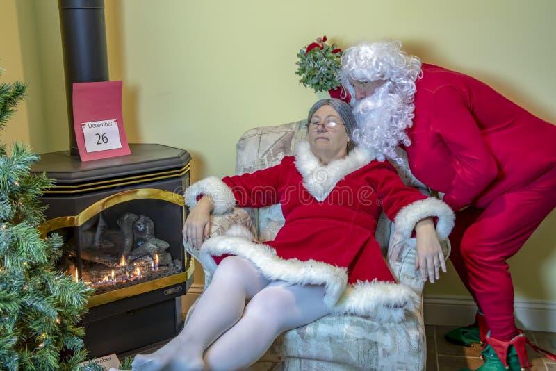 Papá Noel que se escabulle a la señora con el muérdago imágenes de archivo libres de regalías