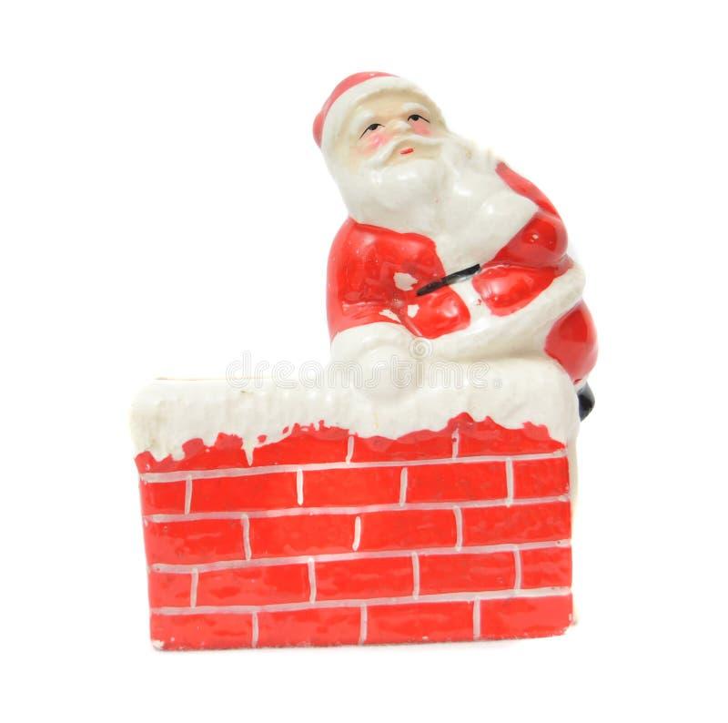 Papá Noel que se reclina sobre una chimenea foto de archivo