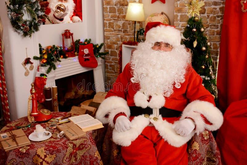 Papá Noel que se sienta en el árbol de navidad, cerca de la chimenea fotos de archivo libres de regalías
