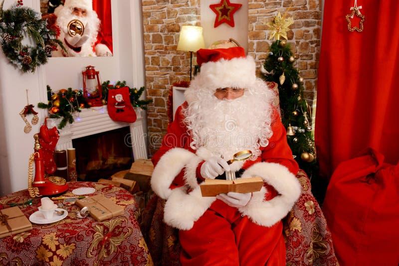 Papá Noel que se sienta en el árbol de navidad, cerca de la chimenea y leyendo un libro imágenes de archivo libres de regalías