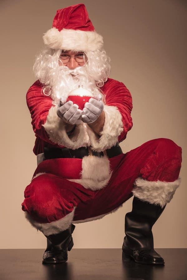 Papá Noel que sienta y que presenta la bola de la Navidad foto de archivo libre de regalías