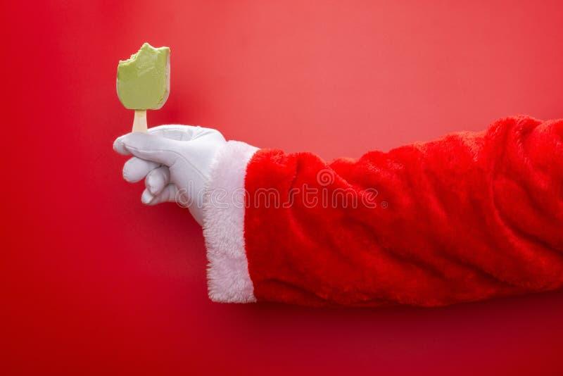 Papá Noel que sostiene el polo de la haba verde con algunas mordeduras delante de un fondo rojo imagen de archivo libre de regalías