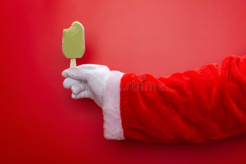 Papá Noel que sostiene el polo de la haba verde con una mordedura delante de un fondo rojo imágenes de archivo libres de regalías