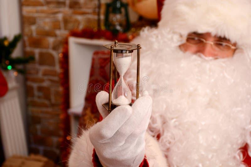 Papá Noel que sostiene el reloj de arena que indica la Navidad está cerca imagenes de archivo