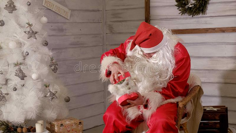 Papá Noel se está sentando en una silla y está intentando rellenar un juguete como regalo fotos de archivo