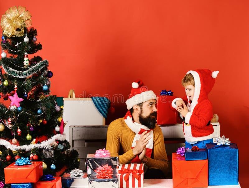 Papá Noel y el pequeño ayudante entre las cajas de regalo acercan al árbol de abeto imágenes de archivo libres de regalías