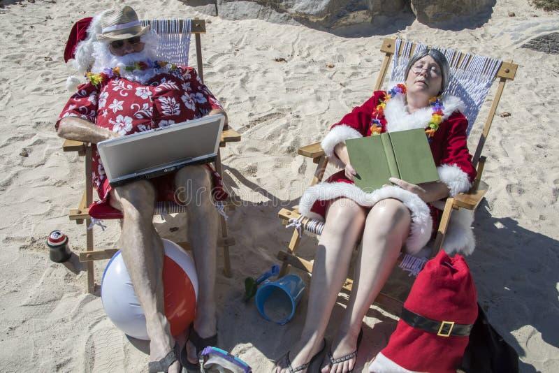 Papá Noel y lectura y funcionamiento de señora Claus en la playa fotografía de archivo libre de regalías