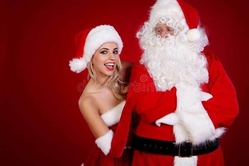 Papá Noel y muchacha asombrosa de la Navidad imagenes de archivo