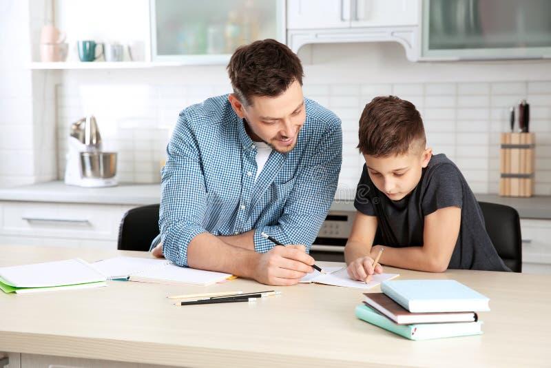 Papá que ayuda a su hijo con la preparación imágenes de archivo libres de regalías