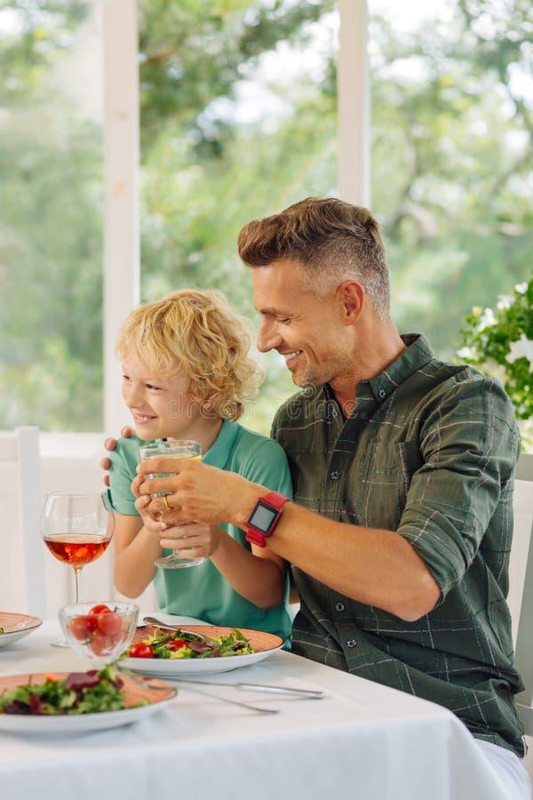 Papá que cuida que lleva el reloj elegante que da a su hijo el vidrio de limonada fotos de archivo