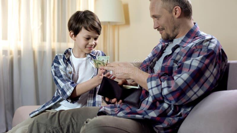 Papá que da efectivo de la cartera al hijo para los nuevos juguetes, dinero suelto del niño, finanzas foto de archivo libre de regalías