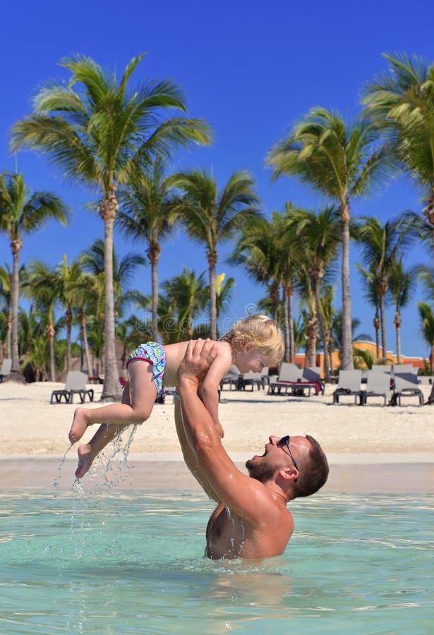 Papá que detiene al niño del bebé en vacaciones tropicales de la playa del mar de las manos fotografía de archivo