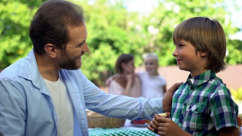 Papá que habla con la mamá del rato del hijo que tiene conversación con la hija, relaciones de la confianza imagen de archivo