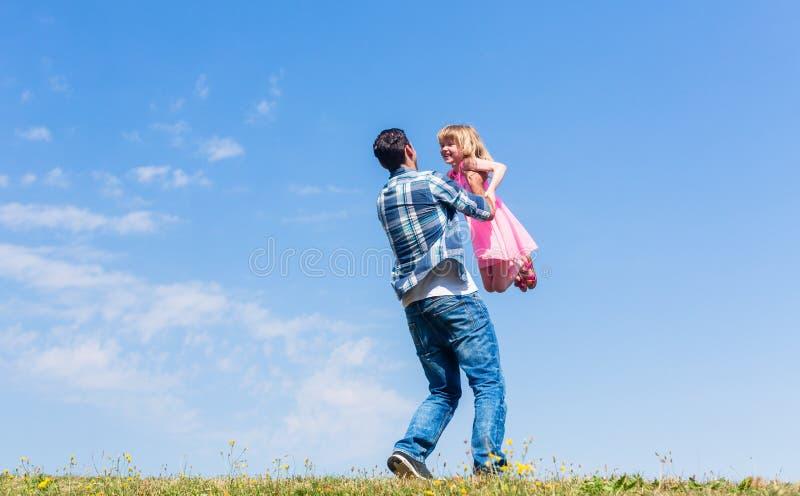 Papá que hace girar alrededor a su hija foto de archivo