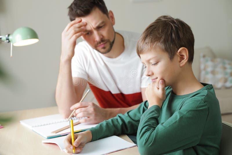Pap? que lucha para ayudar a su hijo con la asignaci?n de escuela imágenes de archivo libres de regalías