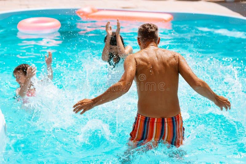 Papá que salpica el agua en hijo y esposa mientras que divirtiéndose en piscina imagen de archivo