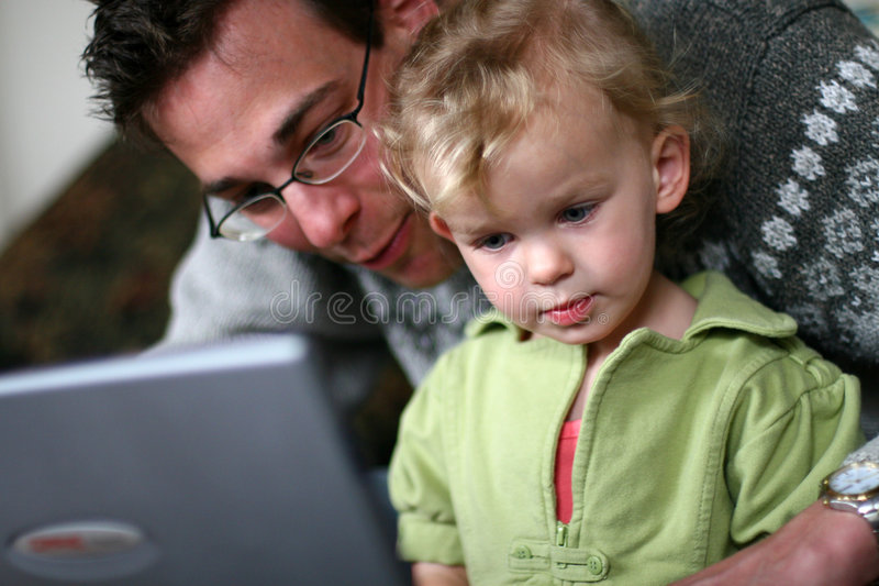 Papá y bebé en el ordenador imágenes de archivo libres de regalías