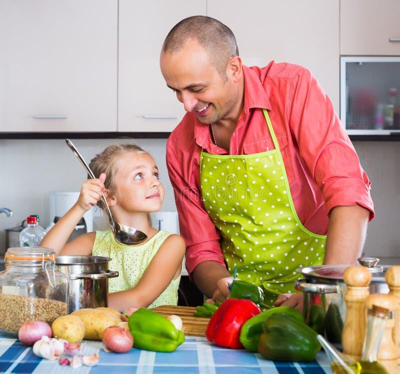 Papá y el pequeño cocinar de la hija fotos de archivo