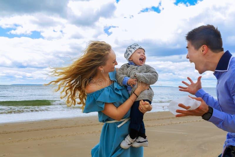 Papá y mamá que juegan con el hijo joven en la playa imágenes de archivo libres de regalías
