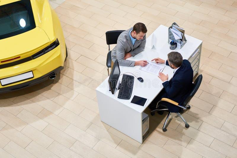 Papéis de assinatura do cliente para comprar o carro fotografia de stock