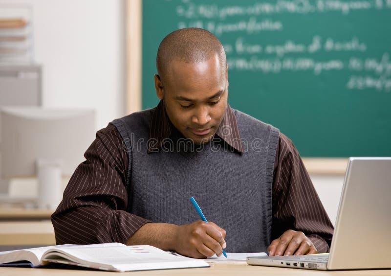 Papéis de classificação do professor na sala de aula da escola fotografia de stock