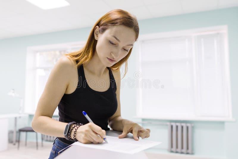 Papéis de negócio de assinatura da mulher bonita nova dentro fotografia de stock royalty free