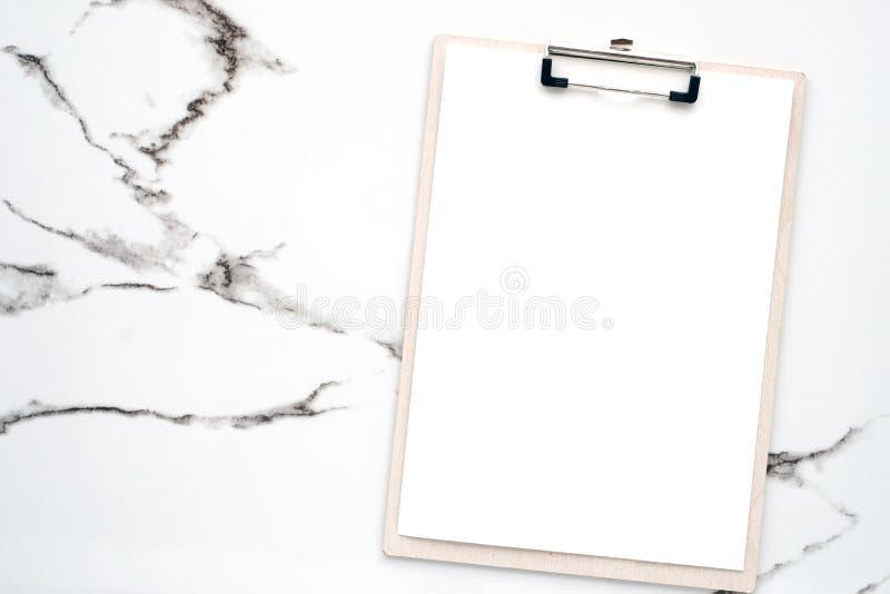 Papéis de nota e placa de grampo brancos vazios no fundo de mármore branco, espaço da cópia para o fundo do projeto da arte fotos de stock