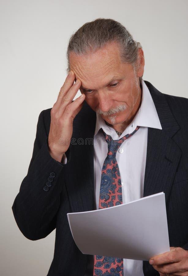 Papéis de revisão forçados do homem de negócio imagens de stock