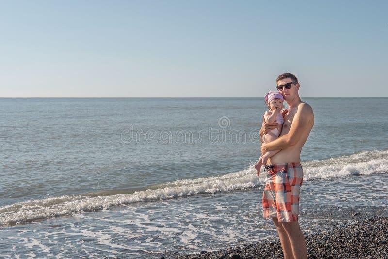 Pap? con la hija en la playa costa, d?a de verano foto de archivo