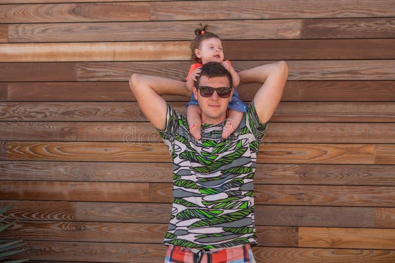Pap? con la hija en un fondo de madera de la pared, d?a de verano fotos de archivo libres de regalías