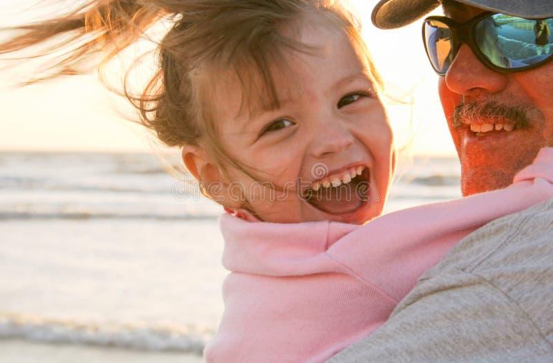 Pap en dochter op het strand tijdens zonsondergang royalty-vrije stock foto's