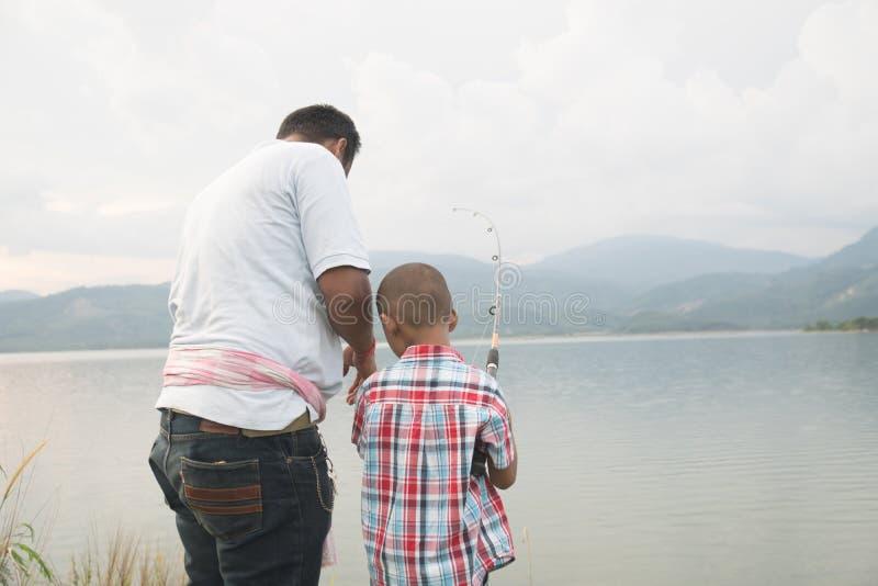 Pap? insegnare alla sua pesca del figlio immagine stock