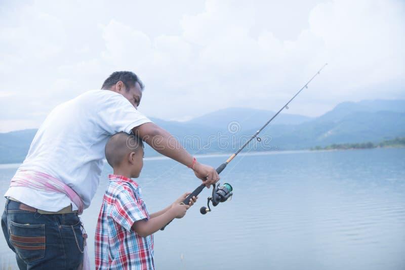 Pap? insegnare alla sua pesca del figlio fotografie stock libere da diritti