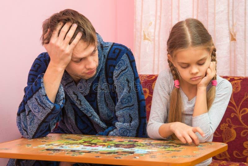 Papa è stanco esaminando sua figlia che raccoglie un'immagine dai puzzle fotografia stock