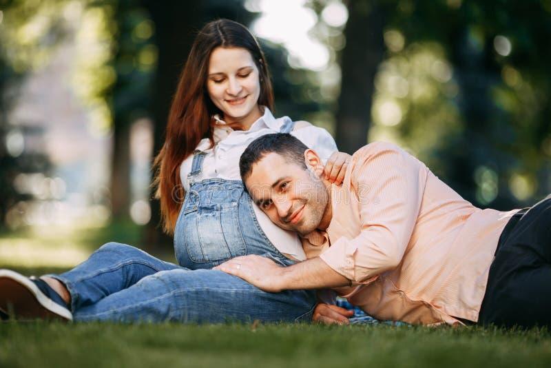 Papa écoutant le bébé se déplaçant à l'intérieur du ventre de mère photo stock