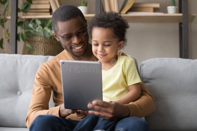 Papa africain heureux et petit fils à l'aide du comprimé à la maison photo libre de droits
