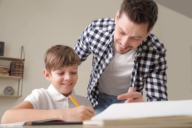 Papa aidant son fils avec la t?che d'?cole image libre de droits