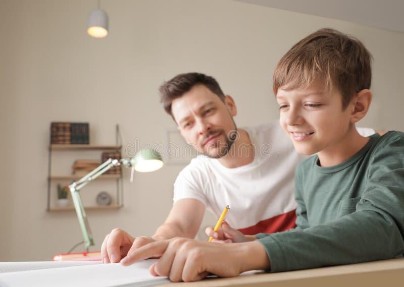 Papa aidant son fils avec la t?che d'?cole images stock