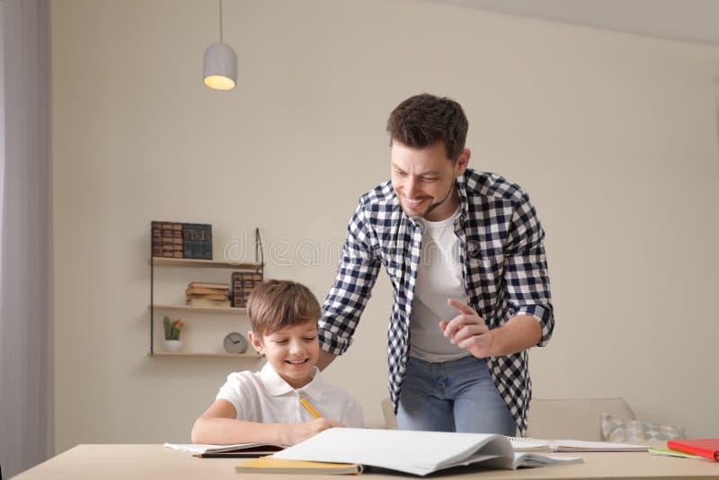 Papa aidant son fils avec la t?che d'?cole photographie stock