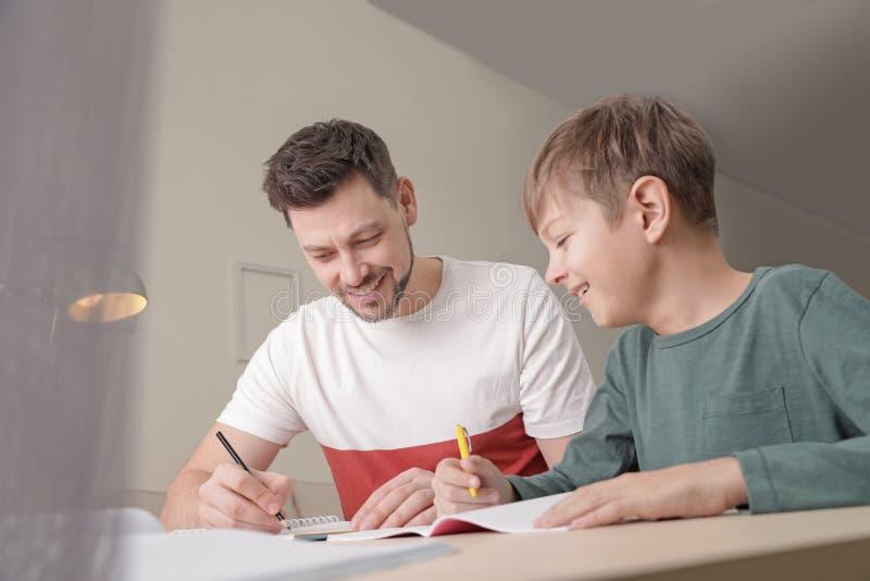 Papa aidant son fils avec la t?che d'?cole photos stock