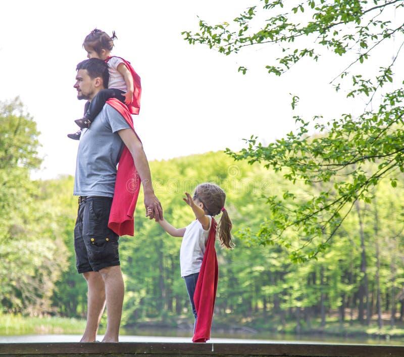 Papa avec deux filles, jeux un superhéros photographie stock libre de droits