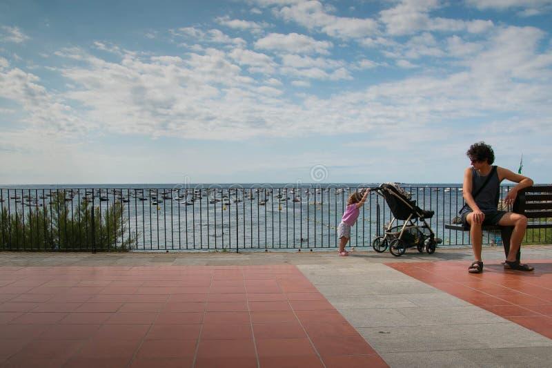 Papa avec la fille d'enfant en bas âge déplaçant sa poussette sur une promenade dedans photo libre de droits