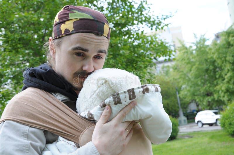 Papa avec le bébé dans la marche extérieure de bride photo stock