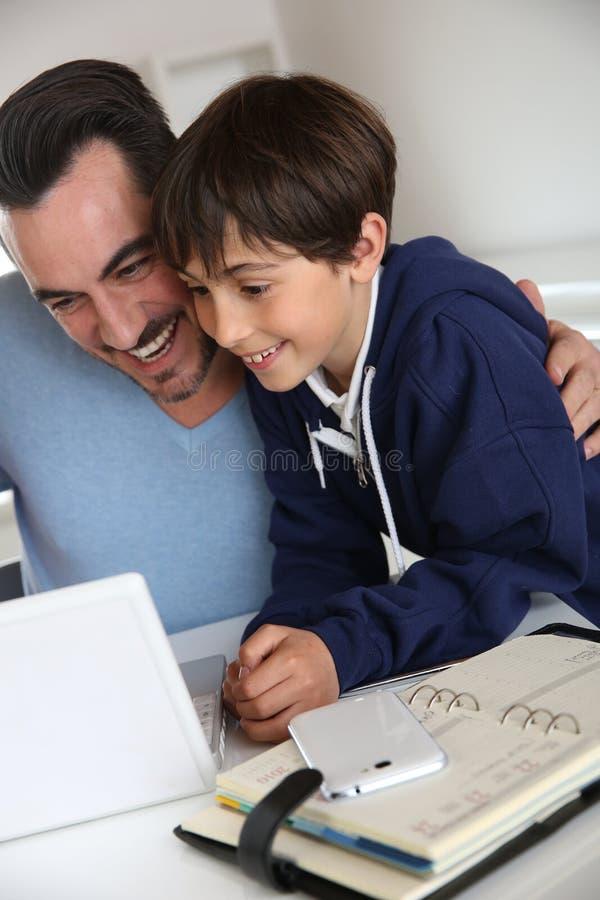 Papa avec le fils relié sur l'Internet photos libres de droits